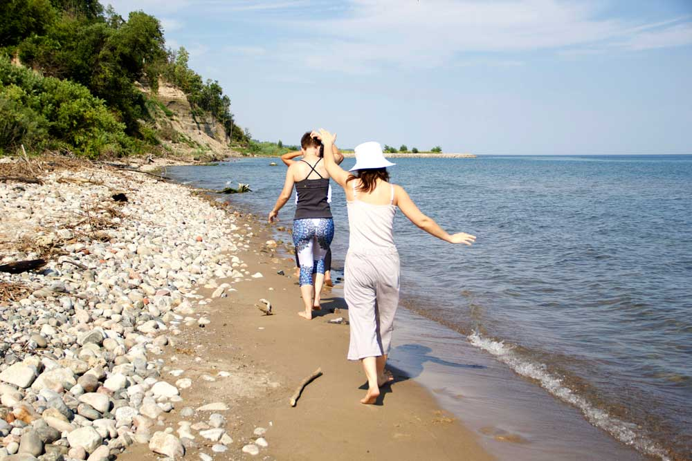 3 sisters walking along the beach barefoot