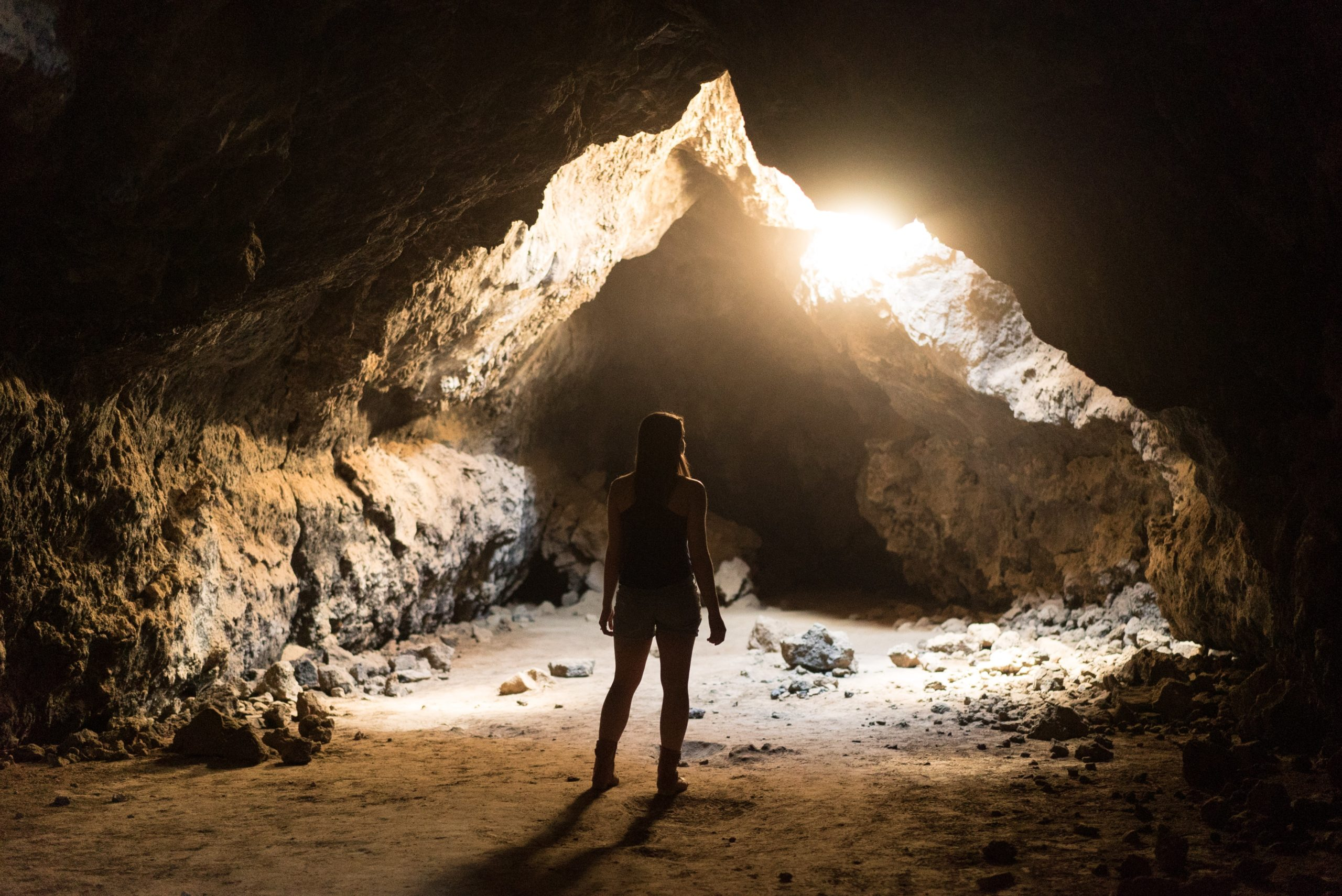silhouette-of-a-woman-at-the-mouth-of-a-cave-with-light-streaming-in